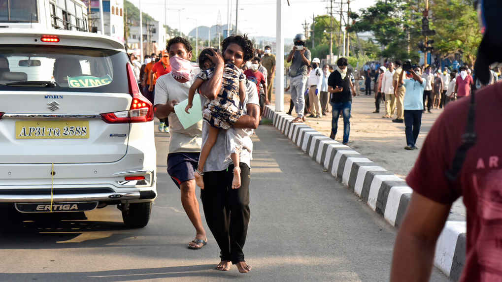 A man runs carrying a child after the gas leak in Visakhapatnam on Thursday, May 7, 2020.