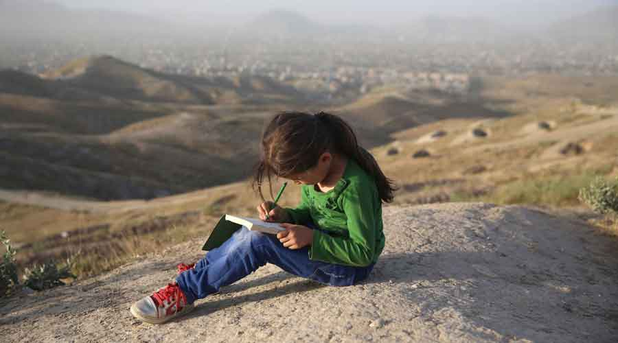 Sadia Shirzad, 7, studies on a hilltop on the the outskirts of Kabul, Afghanistan, on Tuesday