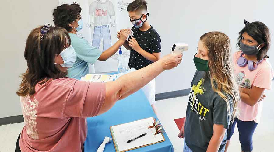 Teachers check the temperature of students at a school in Wylie, Texas