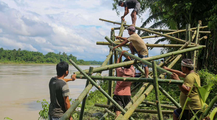Villagers erect a bamboo structure (bamboo porcupines) on the bank of Dihing River to check erosion at Naharkatia under Dibrugarh district of Assam, Sunday, June 28, 2020.