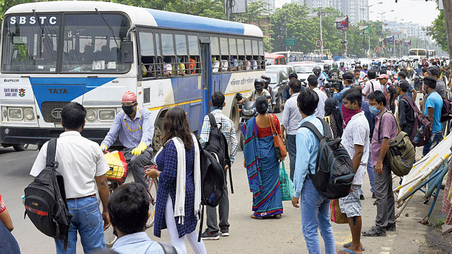 Commuters wait for buses on BT Road on Monday morning.