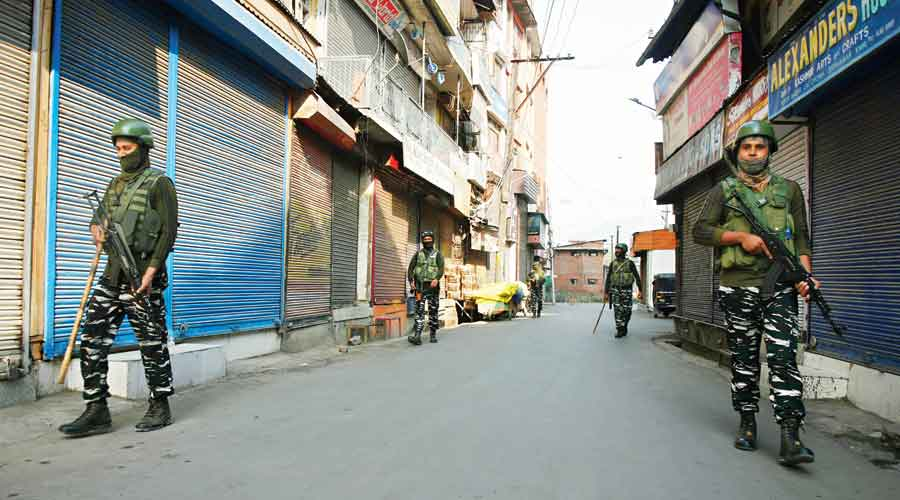 Security personnel patrol a closed market in  Srinagar on Saturday
