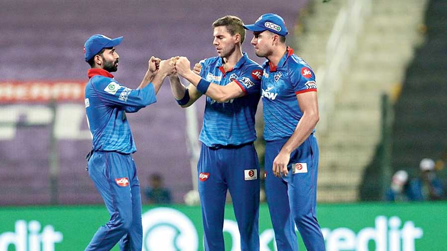 Anrich Nortje (centre) celebrates with teammates after  taking the wicket of RCB's Devdutt Padikkal in Abu Dhabi on Monday.