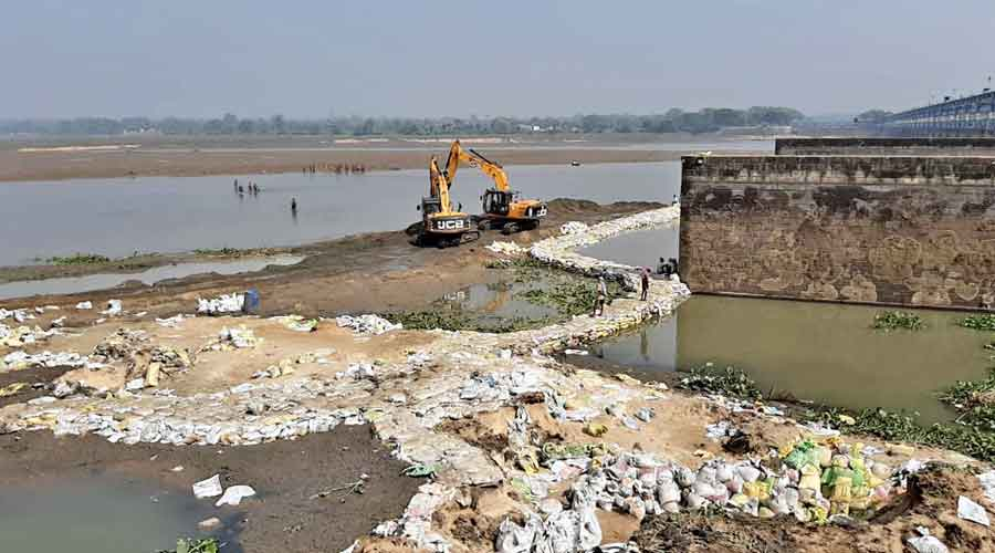 An earthmover and sandbags on the site of the damaged Durgapur Barrage on Monday
