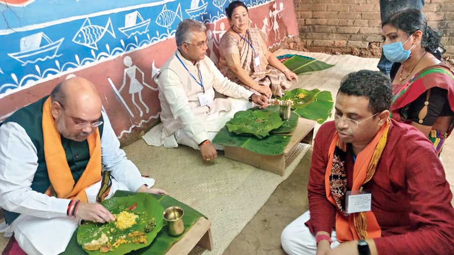 Amit Shah and other BJP leaders have lunch at the home of tribal farmer Bibhishan Hansda in Bankura on Thursday.