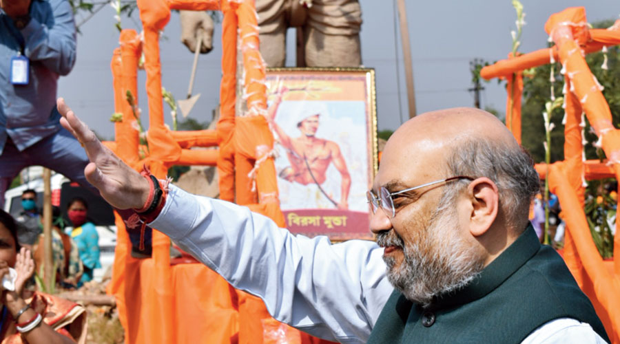 "Union home minister Amit Shah waves to party supporters in Bankura on Thursday after paying homage to a tribal hunter's statue that BJP leaders had mistaken for a statue of ""Bhagwan Birsa Munda"". At the foot of the statue is a picture of Birsa Munda that had been placed there after a tribal body had pointed out the mix-up."