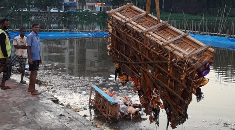 An idol being hauled out of the water at Debi Ghat with a crane