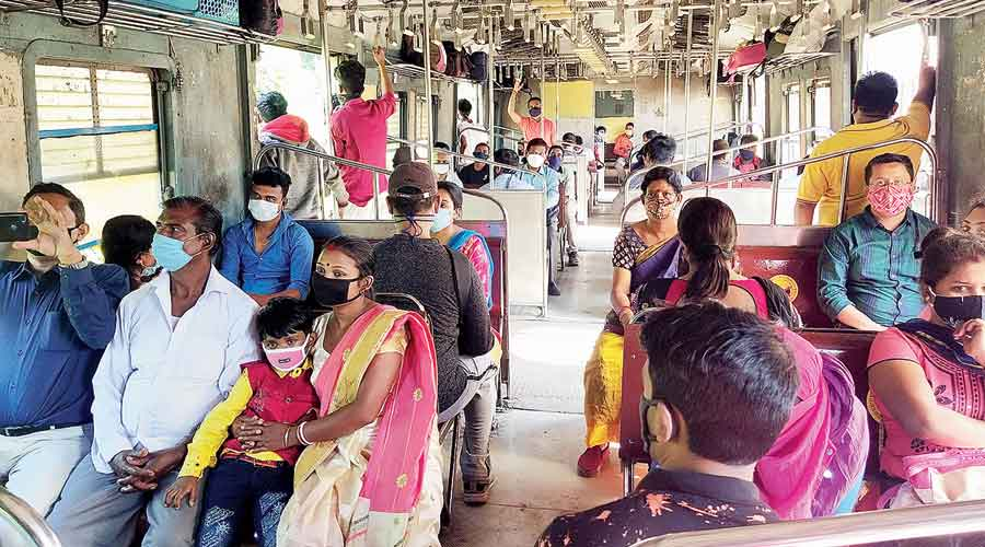 Passengers flout social distancing norm, as appealed by railway authorities, on a Sealdah bound local train