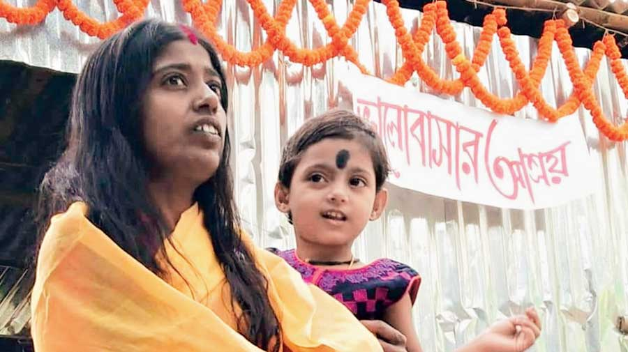 Babla Pramanik's wife Pinki with her daughter in front  of the rebuilt house.