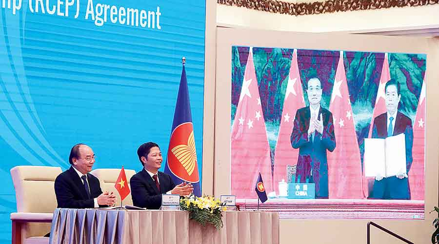 Vietnam's Prime Minister Nguyen Xuan Phuc (left) and trade minister Tran Tuan Anh watch a screen showing Chinese Premier Li Keqiang and commerce minister Zhong Shan holding up the RCEP agreement, in Hanoi, Vietnam, on Sunday.