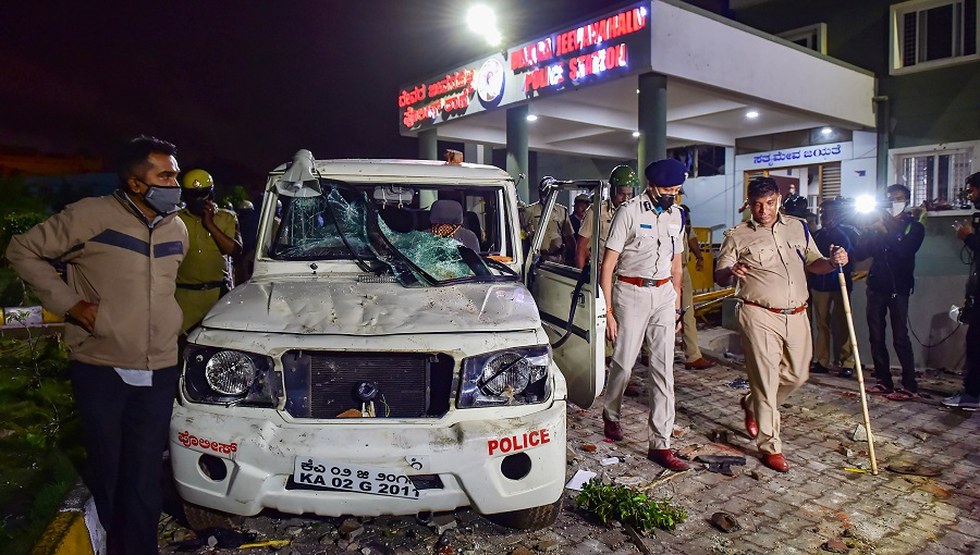 Police stand guard after a mob vandalised a police station following a social media post by a relative of a MLA, in Bangalore on August 12