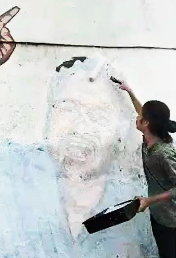 One of the artists paints over the mural