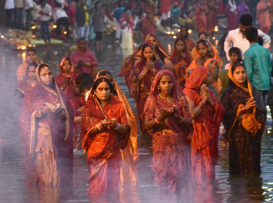 Devotees perform the ritual of offering Morning Arghya to the sun god for the well being of their family at Manaitand Chhat Talaw in Dhanbad on the occasion of Chhath Puja on Saturday morning