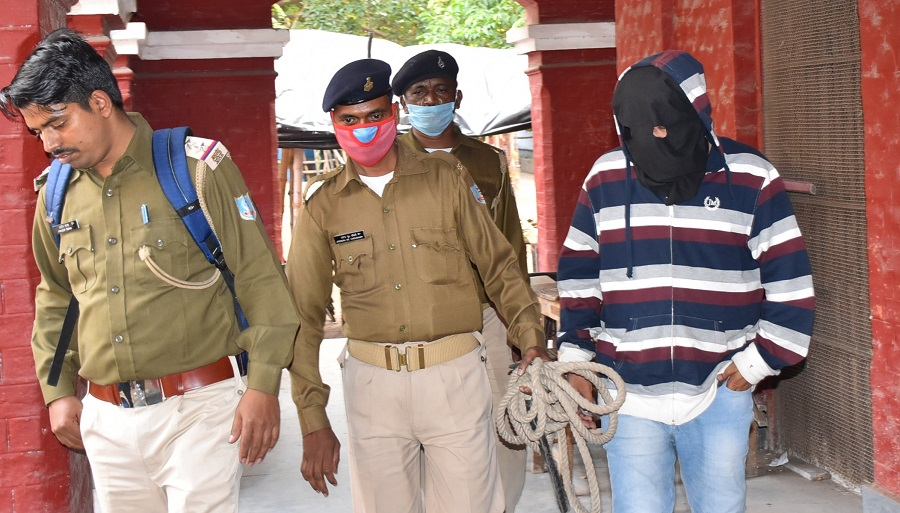 Rape accused Badal Gautam (face covered) being taken to Dhanbad court today.