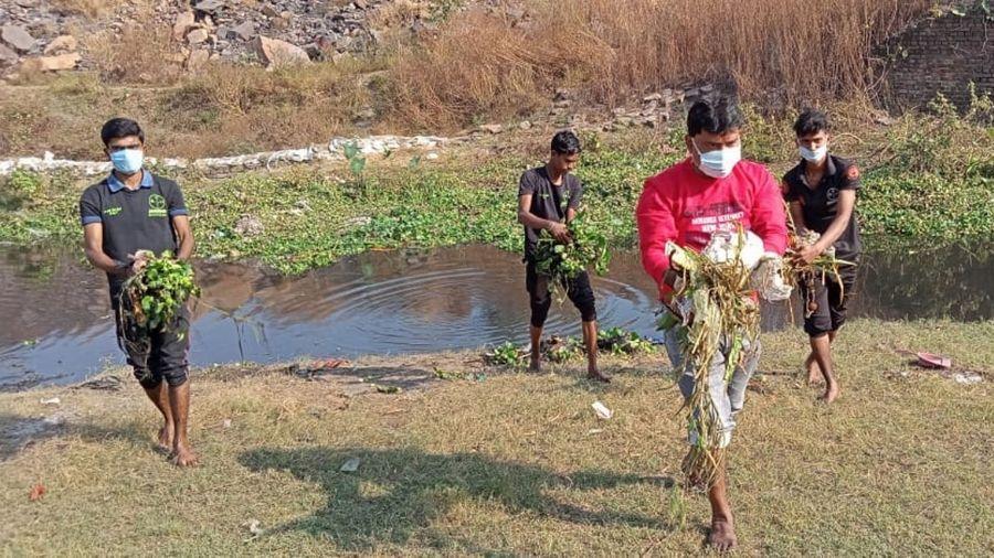 Volunteers of NGO 'Samadhaan' cleaning the Lodna Talaw in Jharia, Dhanbad on Sunday.