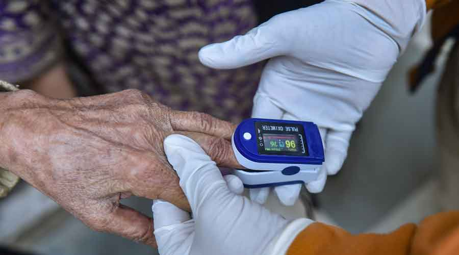 Volunteers use an oximeter to measure the oxygen level during a door-to-door campaign to check symptomatic COVID-19 residents Delhi