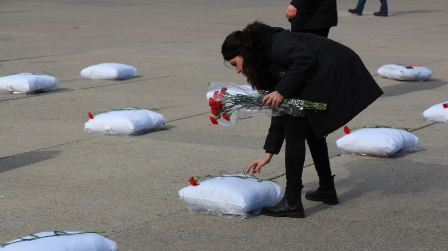 A group of Azerbaijani people stage a protest by laying 93 pillows and red carnations with the names of 93 Azerbaijani civilians who were killed during Armenian attacks, Toronto, Canada