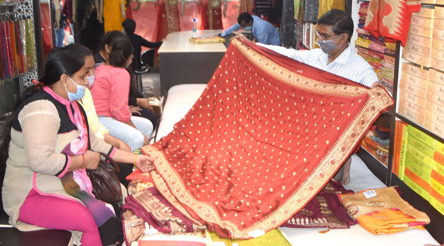 Ahead of marriage (Lagan) season families purchasing sarees at a saree shop in Park Market, Hirapur in Dhanbad on Monday.