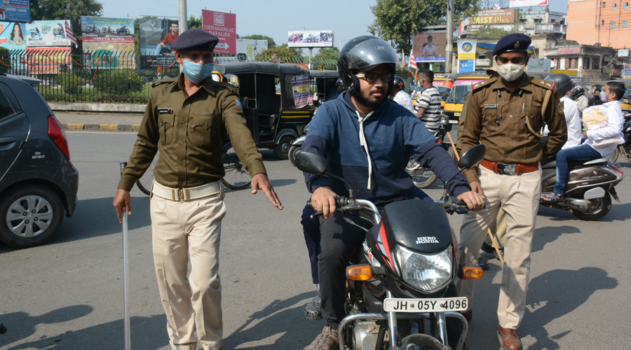 Police stop a man on a two-wheeler for not wearing a mask near Sakchi roundabout in Jamshedpur on Monday.