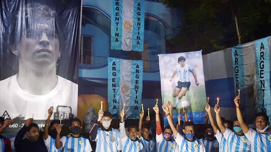 Fans of Diego Maradona hold candles to pay the footballer homage in Calcuuta on Thursday.