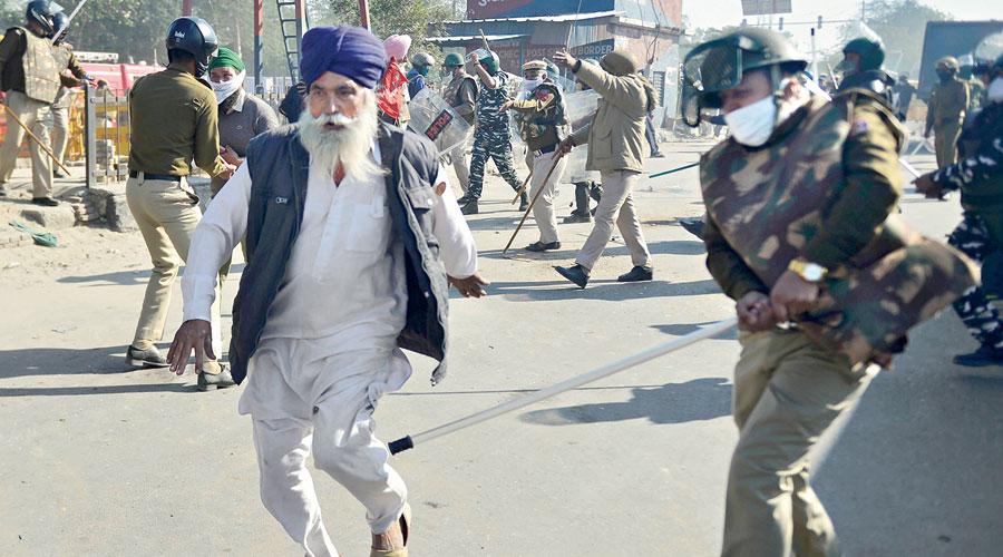 A policeman baton-charges an elderly farmer at the  Delhi-Haryana Singhu border on Friday.