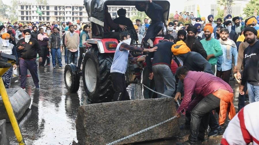 Farmers remove a cement barricade at Ambala during their 'Delli Chalo' march on Thursday.