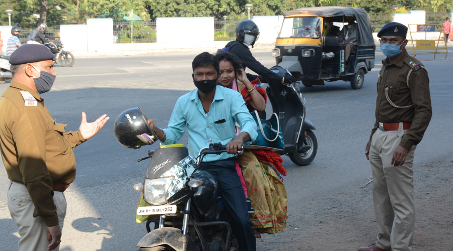 A policeman stops a family on a two-wheeler near a testing centre at Golmuri in Jamshedpur on Saturday.