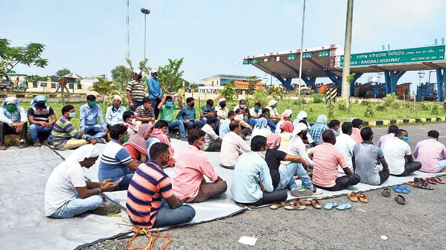 Workers demonstrate near the toll plaza in Baishnabnagar on Wednesday.