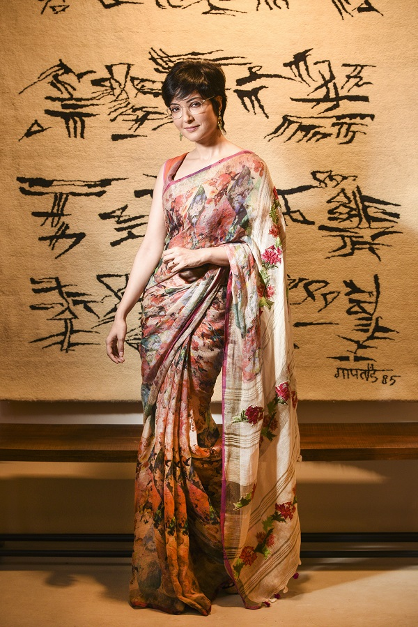"Arpita cuts a picture of cool comfort in this Abhishek Dutta handwoven linen sari with digital floral and geometric print. The pallu, with hand-embroidered bold flower motifs, lends a touch of contrast to the busy print on the body. Traditional Rajasthani earrings complete the look.  (Sari: Rs 11,500, Earrings: Rs 4,950)   ""This sari is easy to drape and very comfortable too. It is ideal for the season since Pujas in Calcutta can be really hot and humid. You can wear it for anjali or as an evening outdoor do. Instead of a blouse, you can wear it with a shrug or jacket,"" said Dutta."