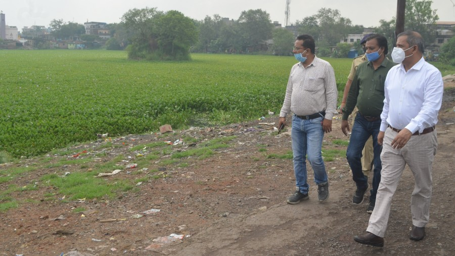 Dhanbad municipal commissioner Satyendra Kumar (in white shirt) and other officials during an inspection of the pond at Jharia, Dhanbad, on Friday.