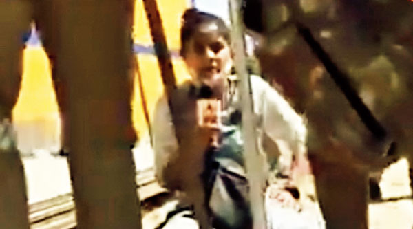 ABP News reporter Pratima Mishra sits on the ground and reports after police stopped her near the village in Hathras