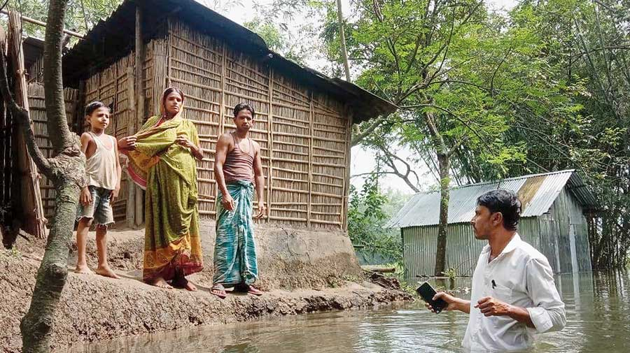 A panchayat member wades through the water to meet villagers in Chanchal, Malda, on Sunday.