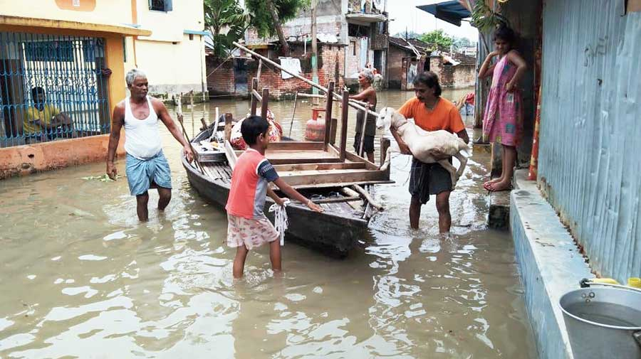 People use a country boat to shift their belongings from an inundated area in Malda on Sunday.