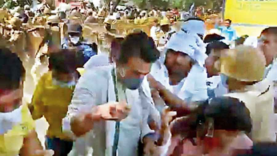 Video clips show former MP Jayant Chaudhary (second from left) being shielded by his supporters as Uttar Pradesh police mount a lathicharge near the  house of the victim in Hathras on Sunday