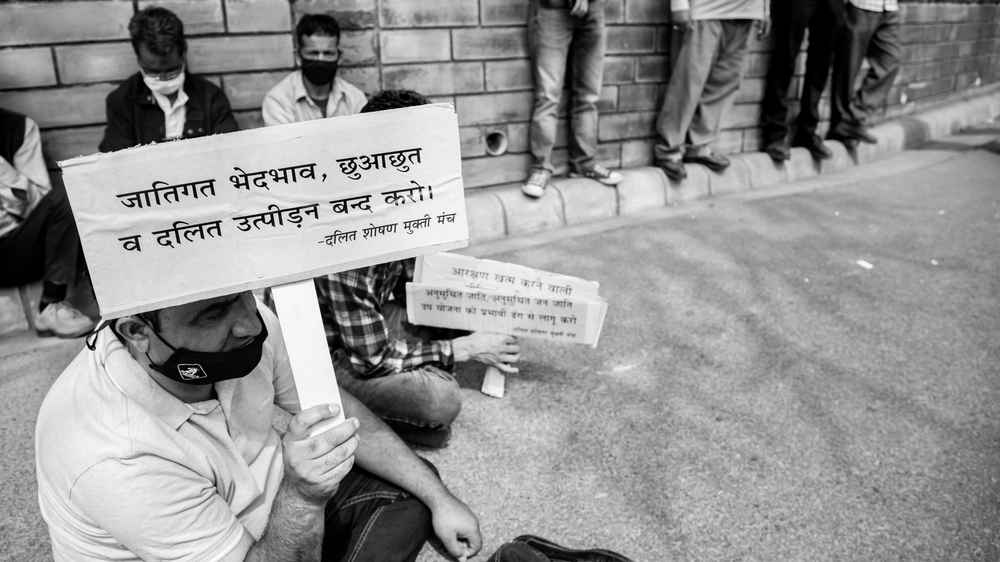 September 16, 2020: A protestor sitting on ground while holding a placard during a protest held by people of dalit community outside the HP Vidhan Sabha.