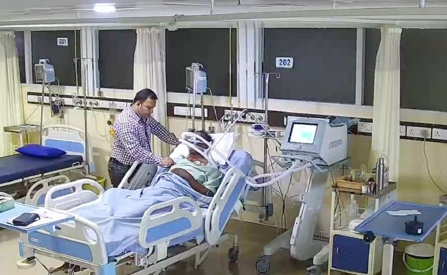 A doctor treats a patient in an ICU of a hospital.