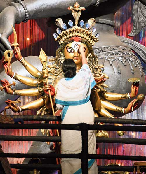 Chief minister Mamata Banerjee paints the eye of the Durga idol at the pandal of Chetla Agrani Club on Monday.