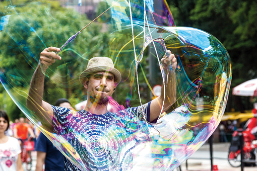 A man was blowing tent-sized bubbles through which the street took a Dali-esque appearance