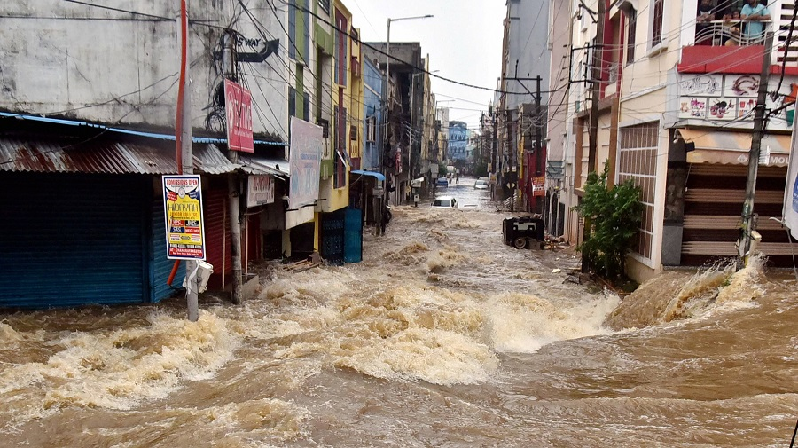 Floodwater gushes through a street following heavy rains, at Falaknuma, in Hyderabad on Wednesday.
