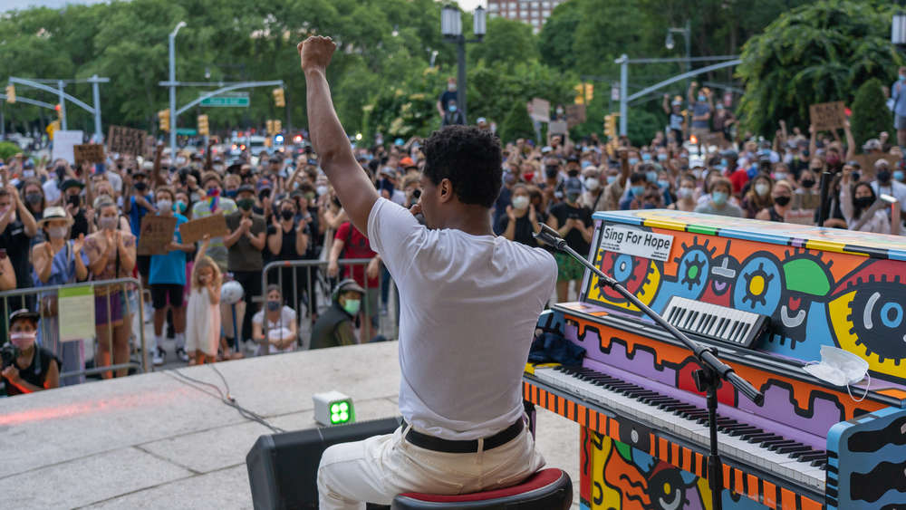 Musician Jon Batiste speaks to gathered crowds between songs as he performs live on Juneteenth on the steps of the Brooklyn Public Library at the Grand Army Plaza.