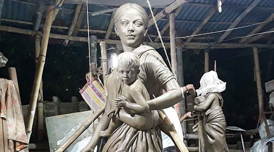 The idol of a migrant worker mother, a shirtless toddler (Kartick) in her arms, that will  be worshipped as Goddess Durga at Barisha Club in Behala this year