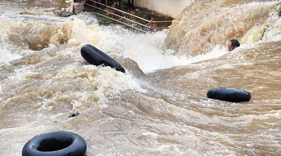A man struggles to stay afloat in gushing floodwaters