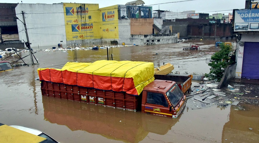 Vehicles lie partially submerged in floodwater following heavy rains, at Falaknuma, in Hyderabad on Wednesday.
