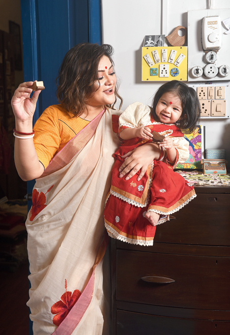 """2. Antahkarana looked like a cupcake in this shiuli jamdani sari. """"You can't think of a Puja without shiuli flowers. This Puja we have launched saris and dhotis for kids,"""" said Parama. Mom Koneenica draped a hibiscus sari. The wooden animal motif blocks on Parama's table ensured that the little one was engaged enough to flash her cutest smile."""