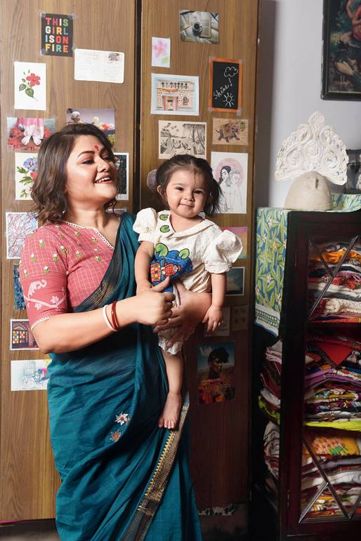"""4. While Koneenica paired a hand-embroidered Mangalgiri shiuli sari with a jamdani blouse with hand-embroidered flowers, her candy-sweet daughter slipped on a shikara dress. """"We are calling this the Firdous dress. I think we have missed travelling for Pujas this time. So, I thought of bringing alive a favourite destination, like Kashmir. Antahkarana looks like the girl in the dress, with apple-red cheeks,"""" said Parama."""