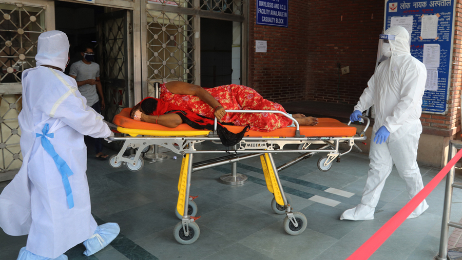 A health worker and patient relative carry a Covid-positive woman on a stretcher at City hospital in Delhi,  July, 2020.
