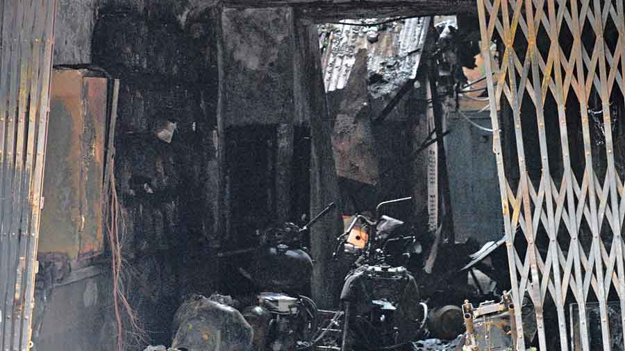 Charred two-wheelers and the electric meter box at the building's entrance