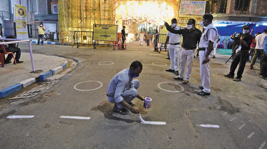 The 10-metre boundary being drawn outside the Mudiali puja pandal on Monday evening.