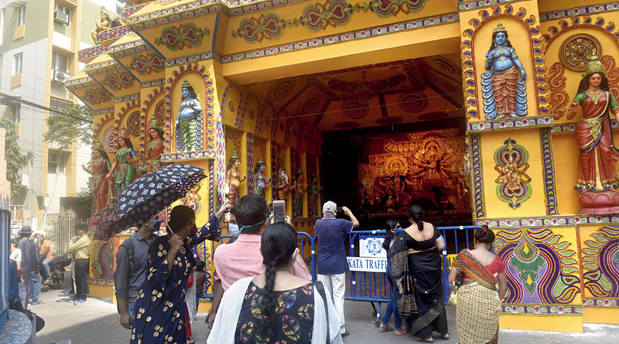 Visitors take photographs at the entrance to the Ekdalia Evergreen puja pandal. Barricades have been put up at 10 metre from the idol, at the entry to the pandal