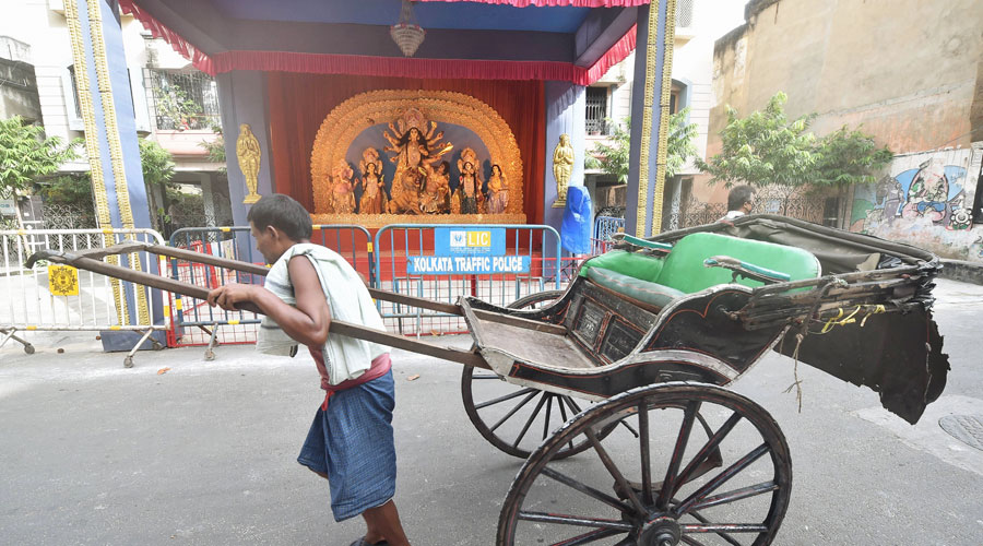 A worker pulls a hand rickshaw as he walks past a community pandal on Wednesday